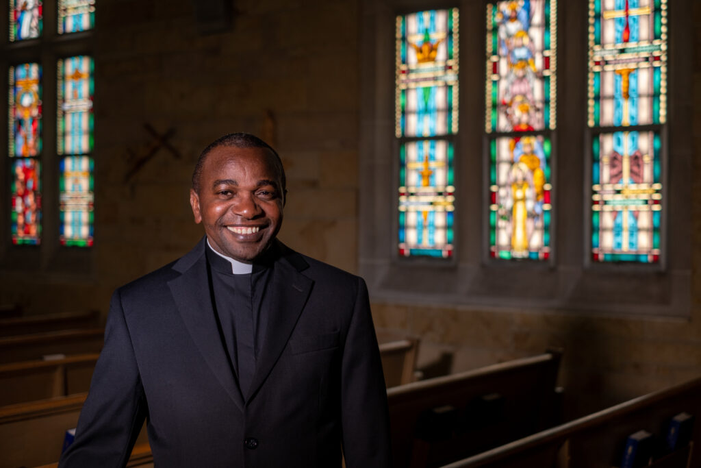 Fr. John Kamwendo in front of stained glass